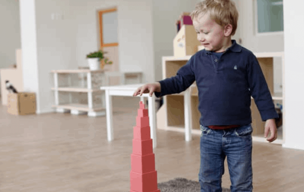 boy playing with the pink tower