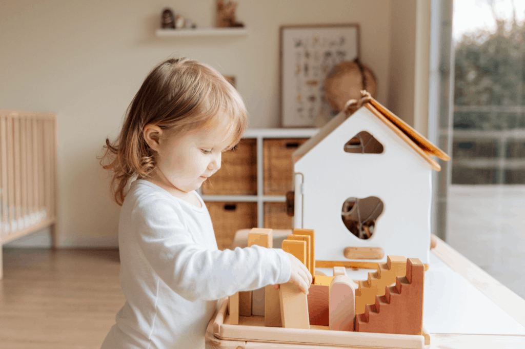 child playing with wooden dollhouse
