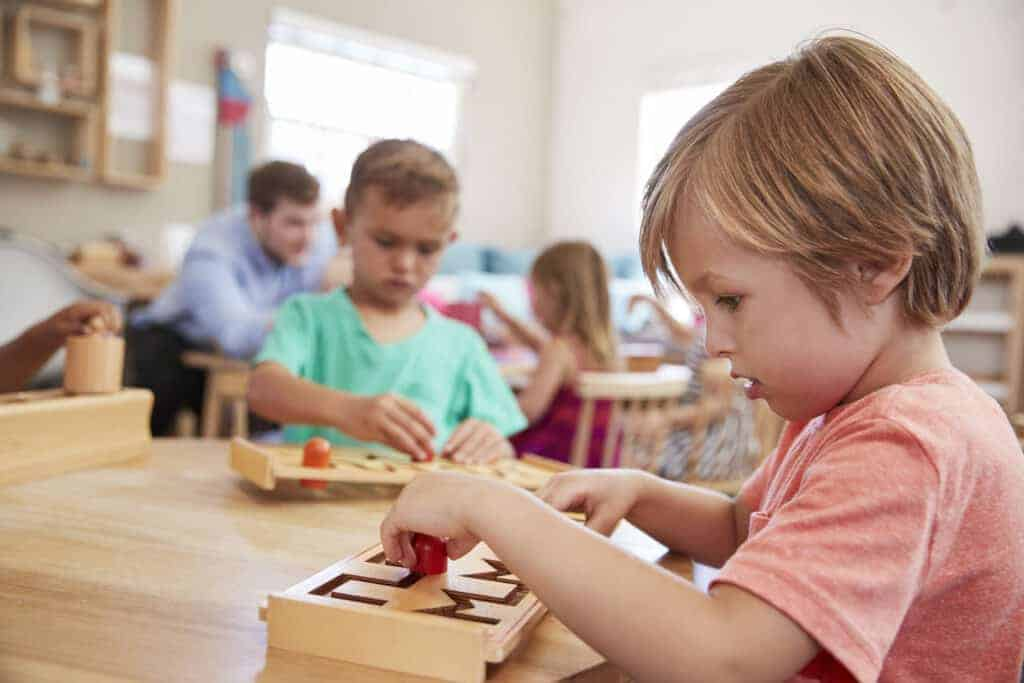 student working at table in montessori school